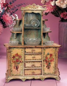 """Theriault's Antique Doll Auctions - French Wooden Cupboard with Hand-Painted Floral Decorations -  19"""" (48 cm.) The doll's cupboard features an elaborate shelving arrangement atop with carved crest,above a four-drawer base with side cupboard doors and arched footing. The cupboard has original pale bronze green painted finish and is decorated with hand-painted wild flower bouquets and borders. Included is a pattern glass berry bowl and matching individual bowls. French,circa 1890."""