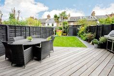Lovely clean garden layout. Nice black stain on the fencing. Like the decking and paving stones.
