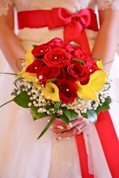 The bouquet, with the dress as background. Bridal bouquet: red roses, yellow calla lilies, and babysbreath