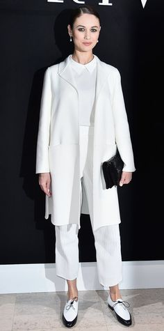 Olga Kurylenko took her front row seat at the Armani Prive spring 2016 show clad in crisp white Giorgio Armani layers, featuring a collared shirt and cropped pants topped with a sleek coat, a black clutch, and two-tone brogues.
