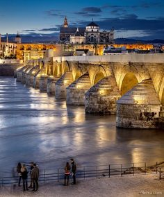 SPAIN / Andalucía - Cordoba. Roman Bridge on Guadalquivir river and Mezquita Cathedral at twilight in Cordoba, Spain. The bridge was built by the Romans in the early 1st century BC.The Via Augusta, which connected Rome to Cádiz, most likely passed through it..