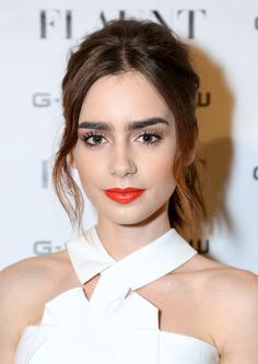 11 of Lily Collins' Best Beauty Looks: Bright orange lips and a neutral face