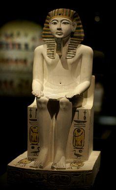 Die Kalksteinstatue zeigt Pharao Amenophis I., den Sohn des Pharao Ahmose. Amenophis I. regierte von 1525 - 1504 v. Chr., die Statue entstand aber erst drei Jahrhunderte später. Amenophis I. trägt das gestreifte Nemes-Kopftuch und ist mit einem geraden Ritualbart dargestellt, der von einem Kinnriemen gehalten wird. Einen solchen Bart trug der Pharao bei der Verrichtung seiner religiösen Pflichten.