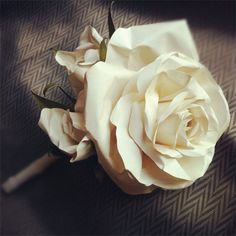 Classic button hole using crafted paper flowers: large rose and two small buds. $14.00, via Etsy.