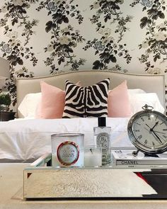 Chic bedroom features a wall clad in Schumacher Pyne Hollyhock Wallpaper lined with a Crate & Barrel Colette Bed dressed on pink pillows and a zebra pillow.