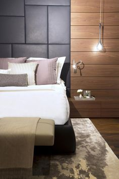 Dark gray leather panels create a sumptuous headboard in this bedroom, especially when paired with the bed's purple and coffee-colored accent pillows. Alongside them, wood panels make a dynamic contrast and fun camouflage for the built-in nightstand.