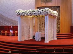 This decadent Wedding altar/chuppah with hanging garland, and mounded hydrangea is quite a romantic spot!