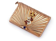 A jewelled and enamelled gold cigarette case  Mark of Carl Blank, St Petersburg, 1899-1904  Rectangular with rounded sides, the body and hinged cover chased with sunburst design from the cabochon sapphire thumb-piece, the cover applied with the crowned entwined initials 'MM' enamelled in translucent red and opaque white, with integral vesta compartment and cord attachment, marked inside body and cover, 3¾ in. (9.5 cm.) wide,  Christie's n°7906.