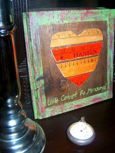 """""""Love Cannot Be Measured"""" sign using pieces of vintage yardsticks"""