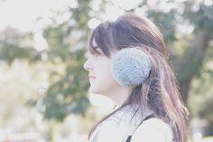 Mulher de perfil usando aquecedor de orelhas cinza no Jardim Botânico de Curitiba.