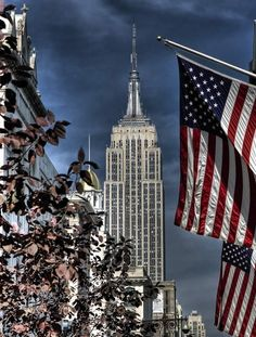 The American flag in the foreground of the Empire State building in New York City. Empire State Of Mind, Empire State Building, Wyoming, Route 66, Hampshire, Places To Travel, Places To Go, Alaska, A New York Minute