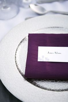 Silver charger plates give the space a glam touch and the purple napkin brings the colour strongly into the place settings