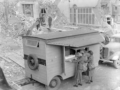 Miss Winifred Ashford and Mrs Pat Macleod open up their mobile canteen in front of a pile of rubble and some severely bomb-damaged houses, London, 1940.