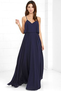 We're absolutely love struck over the Love Runs High Navy Blue Maxi Dress! Navy blue woven poly falls from adjustable straps into a tiered, triangle bodice above a cascading maxi skirt full of volume. Hidden side zipper.