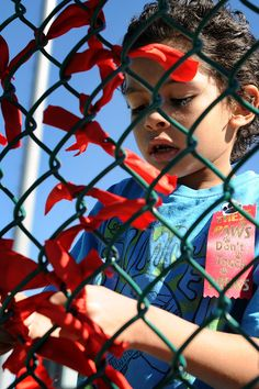 """First grader Roman Blanchard, 6, ties a red ribbon on a fence Oct. 7 during Red Ribbon Week at Springs Ranch Elementary School in Falcon School District 49. Throughout the morning, kindergarten-fifth grade classes lined up with ribbons near a school playground. Counselor Sandy Gates helped them form the phrase """"SRES drug free"""" on a fence. She said the activity starts Red Ribbon Week, a time to teach healthy choices as part of a school wellness plan."""