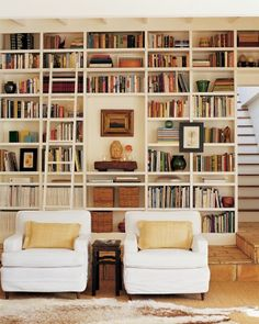 The floor-to-ceiling bookcases are original to this house; woven baskets hold family photos. Wide thrift-store chairs are slip-covered in sturdy cotton.