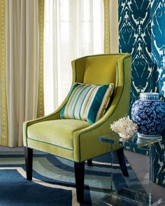 Upholstered Screen in the fabric Torino/Azure. Pinch Pleated Draperies in the fabric Slubby Linen/Ivory, Slubby Linen. Chartreuse with decorative trim. Pinch Pleated Draperies in the sheer linen fabric Lovely Linen/Rice. Lance Chair in the fabric Banks Quince with welting in the fabric Banks/Calypso. Pillow in the fabric Carlow/Prussian.