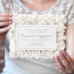"""An invitation that sits on a delicate bed of paper flowers says """"this wedding will be classy as hell."""""""