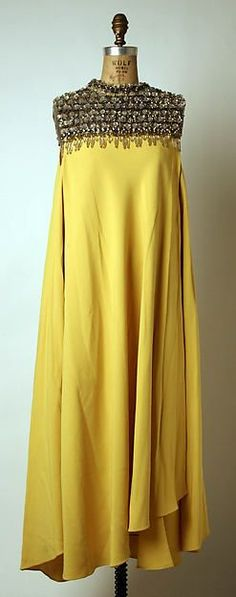 sleeveless yellow cream evening dress with heavy beading around the neck; slight drape, asymmetrical hem; Madame Gres 1962