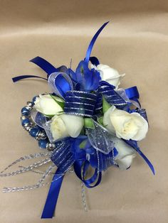 A wrist corsage featuring white tea roses and blue delphinium with silver and blue ribbon accents Price - $37.95 #promflowers #prom2016 #blueflowers #wristcorsage