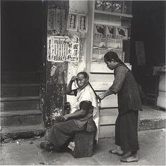 This photograph of a woman having her hair braided by a street beautician was taken by Hedda Morrison in Hong Kong in late 1946 or strap to keep her hair in place throughout the braiding process. According to the Powerhouse Museum collection record:  Both women wear woven cotton trousers