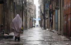 A Palestinian woman walks in the street during heavy rain in Al Shatea in the west of Gaza City, April 12, 2015. (Photo by Mohammed Saber/EPA)