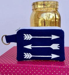 Perfect for the on-the-go woman who doesnt want to lug a purse or wallet around, clip this mini zipper wallet to your keys and hit the road! The arrows are screen printed by hand in Northwest Indiana, making each pouch unique. This navy blue wallet is the perfect size to hold:  * Credit, debit and loyalty cards * Cash and coins * Earbuds * IDs * Lipstick and chapstick * Hair ties and bobby pins * Feminine hygiene products  Features:  * Secure zipper closure * Screen printed design * Printed…