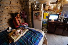 A mother watches television while her month-old boy sleeps. Credit: Kim Ludbrook/EPA