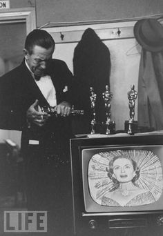 Walt Disney & the four Oscars he won in 1954. He realized that one of them was broken and was attempting to repair it.