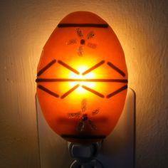 Easter egg nightlight - fused glass.  Orange glass with purple stringers & dichroic flowers.