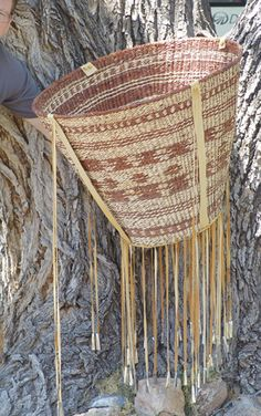 """Apache Burden Basket.  Huge traditional style conical basket with tin cone fringe suspensions and banded geometric design; very good condition. 22"""" x 28"""""""