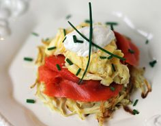 Scrambled eggs on potato pancakes with smoked salmon, sour cream and chives