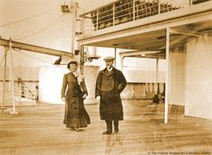 April 11, 1912.  An unidentified couple take a stroll on A-Deck, just by the entrance to the Verandah Palm Court.  Behind them is one of Titanic's many Cargo Cranes, and on the deck above are deck chairs stacked-up ready for use during the voyage.
