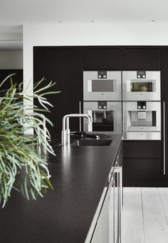 Modern and black kitchen with faucets and appliances from Gaggenau.