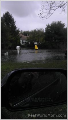 Man in raincoat and waders, walking through the flood water on our street after Superstorm Sandy.