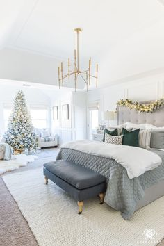 Gray and white Christmas bedroom with a pop of green and modern chandelier