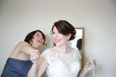 happy bride getting ready with her bridesmaid