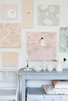 Not a fan of the pastels but the idea of fabric-covered canvases all over a blank wall is intriguing.