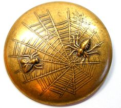 Brass spider web with fly button.