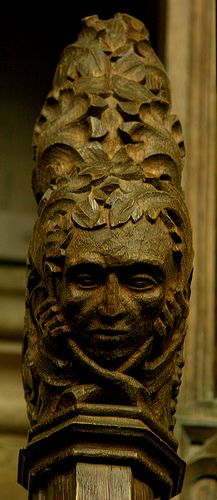Poppy-head: Green Man n the choir stalls, Adderbury church, Oxfordshire. Unlike many green men, this one does not have foliage issuing from his mouth. Rather, he seems to be entwined with foliage, and perhaps attempting to extricate himself from it