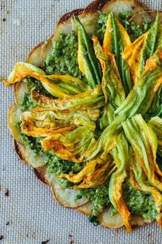 vegan and gluten-free potato crusted pizza with garlic scape pesto and squash blossoms.