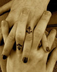 My grandfather had an anchor tattoo on the web of skin between his thumb and forefinger. I've always wanted one too. His had the rope around the anchor, but it had the same simplicity of the ring finger style as seen here. Love this idea for a couple! <3
