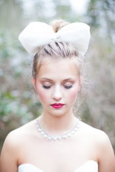Oversized bow hair piece and pretty make up look. #bride #weddinghair #weddingchicks Make Up: Beth Level Artistry ---> http://www.weddingchicks.com/2014/05/01/alice-in-wonderland-wedding-ideas/
