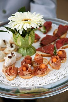 Guests are offered fantastic bite-sized canapes that surround a single white gerbera daisy.