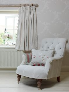 This handmade embroidered Dove in Olive Tree cushion marries up with the grey oxford stripe buttoned back armchair. This very gentle room works in reverse having the walls as the statement with Apple Blossom Pearl/Ivory wallpaper and grey/ivory striped curtains.