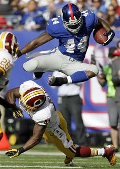 New York #Giants RB Ahmad Bradshaw, top, leaps over Washington #Redskins free safety Madieu Williams for a first down.