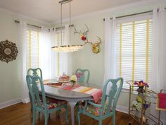 A crystal chandelier hangs above a repainted secondhand table and reupholstered chairs in this funky dining room designed by HGTV's Property Brothers.