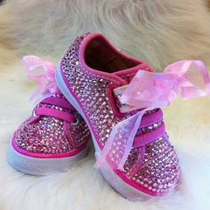 Cute pink bling sneakers for a little girl, with pink ribbon as shoe laces.
