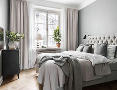 bedroom with lots of gray and neutrals - love the long curtains, bedding in tones of gray, plants, and lots of natural light