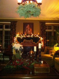 An example of classic formal living room decor.  Lighted pine garland on the mantle under Christmas themed artwork adorned with white lights and birch candles overlooking an understated coffee table adorned with antique Santa dressed in real fur and scrap fabric.  Tying the theme from the formal dining space a fresh garland wreath hangs from the light fixture.  A true classic Christmas.